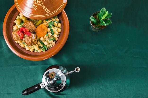 Platte mit essen in der nähe von becher getränk und teekanne