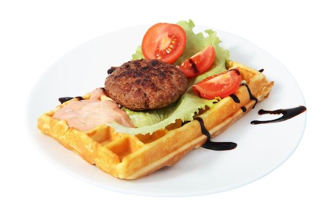 Platte mit fast food, belgische waffel mit beefsteak, geschnittenen tomaten, salat und soße, isoliertes bild auf weißem hintergrund.