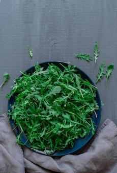 Platte mit frischem grünem rucola auf grauem hintergrund