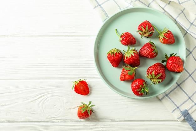 Platte mit frischen erdbeeren und küchentuch auf weißem hölzernem hintergrund, draufsicht und raum für text