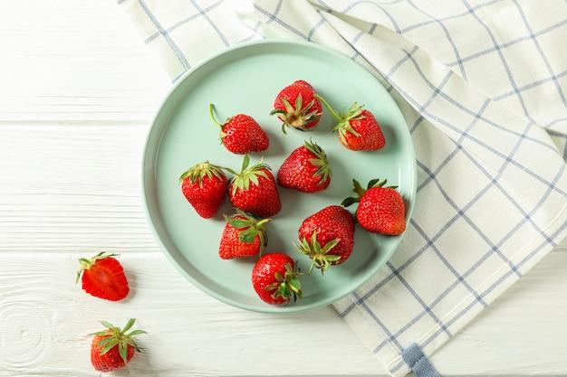 Platte mit frischen erdbeeren und küchentuch auf weißem holztisch, draufsicht und platz für text
