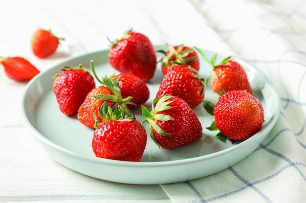 Platte mit frischen erdbeeren und küchentuch auf weißem holztisch, nahaufnahme und platz für text