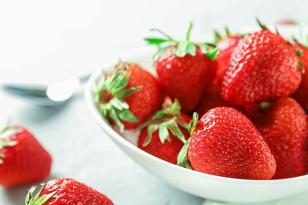 Platte mit frischen erdbeeren und löffel auf weißem holztisch, nahaufnahme und platz für text
