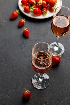 Platte mit frischer erdbeere und glas wein auf schwarzem hintergrund schließen oben