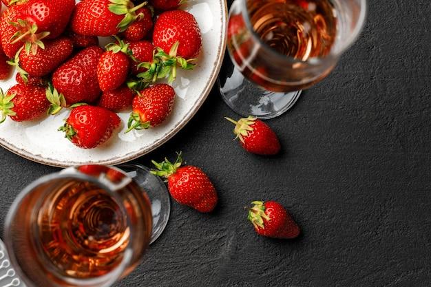Platte mit frischer erdbeere und glas wein auf schwarzem hintergrund