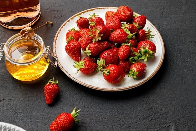 Platte mit frischer erdbeere und glas wein auf schwarzer nahaufnahme