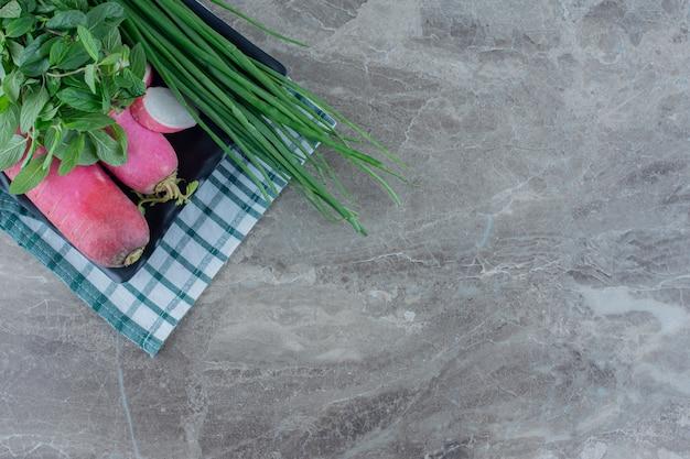 Platte mit frühlingszwiebeln, minze und rübe auf marmor garnieren.