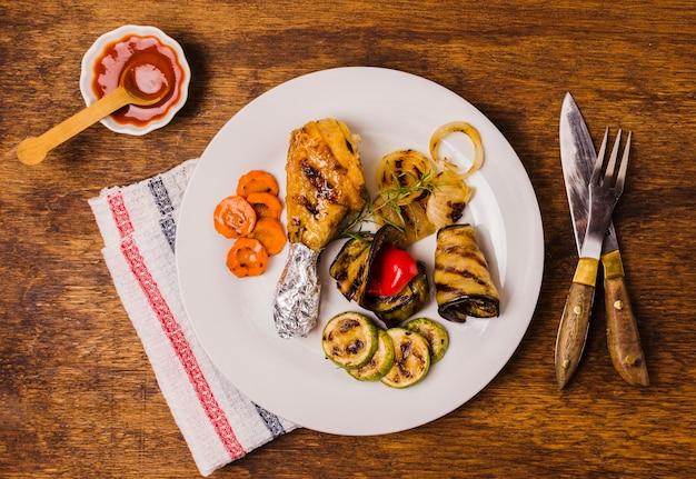 Platte mit gegrilltem hähnchenschenkel und gemüse