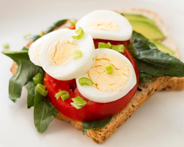 Platte mit gekochtem ei und tomatensandwich