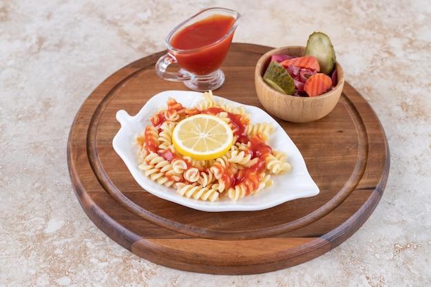 Platte mit gekochten nudeln, ketchup und einer schüssel gemischte gurken auf marmoroberfläche