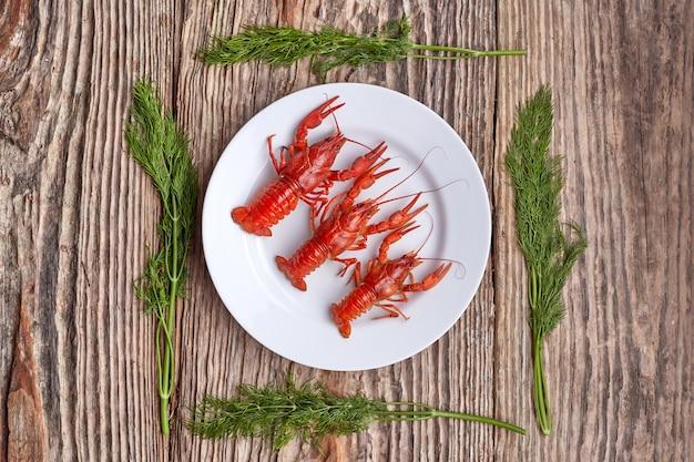 Platte mit gekochten panzerkrebsen auf rustikalem holztisch