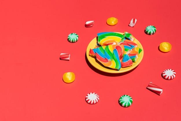 Platte mit geräuchertem lutscher umgeben von süßigkeiten
