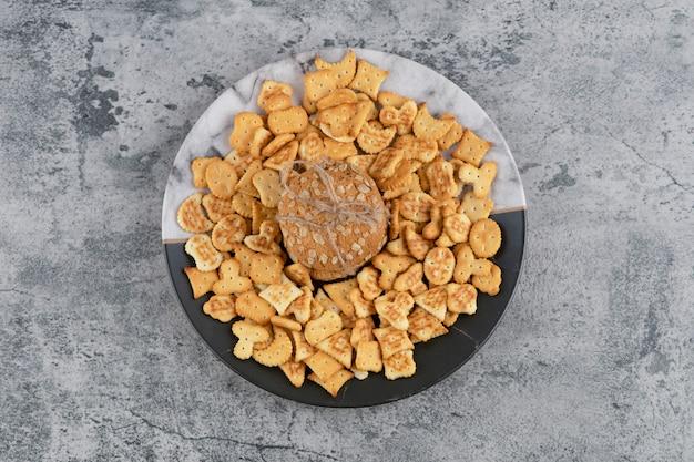 Platte mit gesalzenen crackern und haferkeksen auf marmorhintergrund.