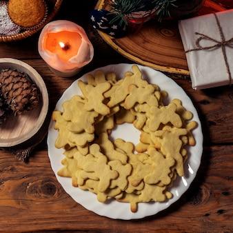 Platte mit geschmackvollen weihnachtsplätzchen, -kerze und -geschenk auf holztisch. ansicht von oben. .