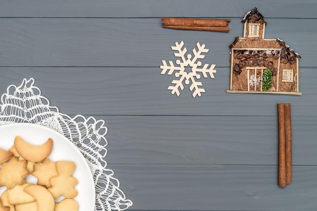 Platte mit geschmackvollen weihnachtsplätzchen mit zimt und dekorativer schneeflocke und haus auf holztisch