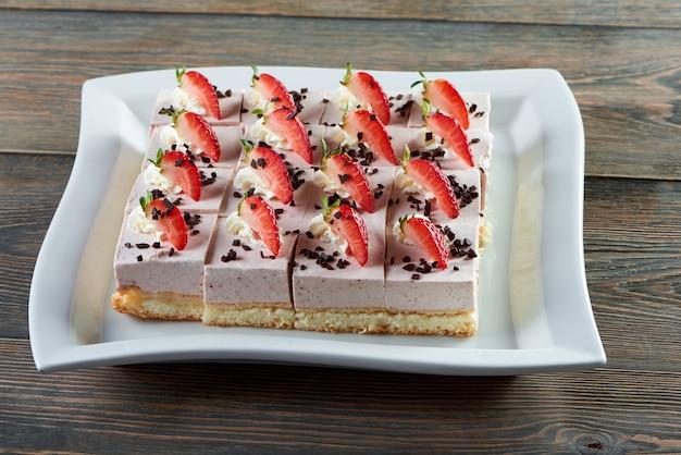 Platte mit geschnittenem käsekuchen verziert mit schokoladenkruste und erdbeeren, die auf hölzernem tischrestaurantcafé-coffeeshop-bäckerei-back-kochendes gebäck süßeres dessertkonzept platziert werden.