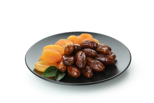 Platte mit getrockneten datteln und aprikosen isoliert auf weiß