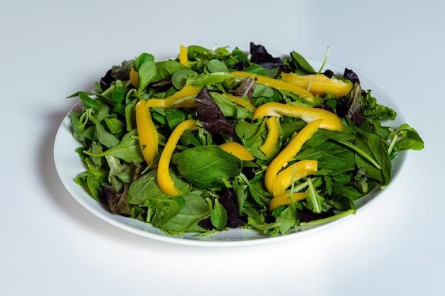 Platte mit grünem salat und gelben paprikaschoten auf einem weißen küchentisch, nahaufnahme, gesunde ernährung und diätkonzept