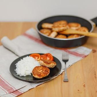 Platte mit hausgemachten lachsfischkoteletts mit reis auf holztisch.