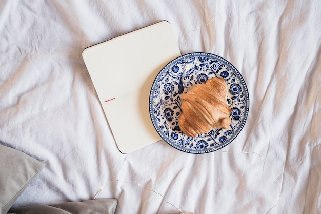 Platte mit hörnchen und geöffnetem notizbuch