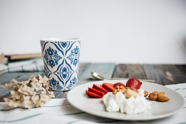 Platte mit hüttenkäse, erdbeeren und nüssen, einem tasse kaffee und tüchern auf holztisch, gesundes lebensmittel, frühstück