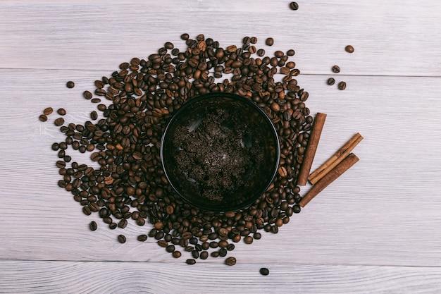 Platte mit kaffee-peeling liegt auf dem tisch zwischen kaffeebohnen
