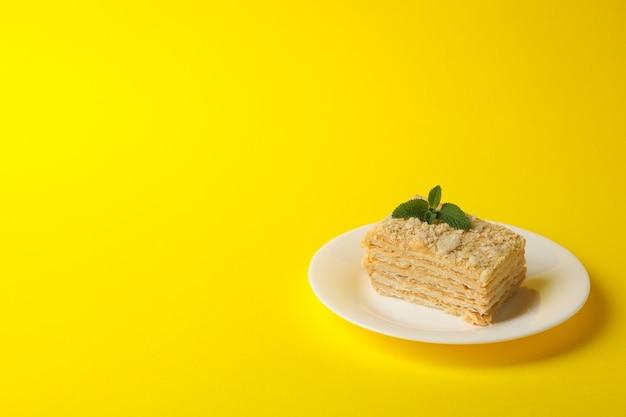Platte mit köstlichem napoleon-kuchen auf gelber oberfläche