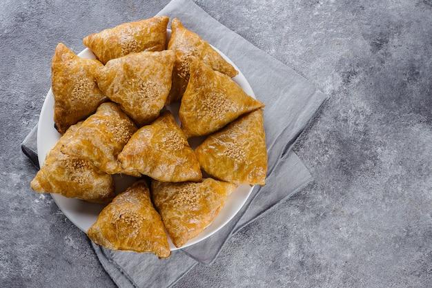 Platte mit köstlichem samosas samsa mit fleisch auf grauem hintergrund, draufsicht. usbekisches essen