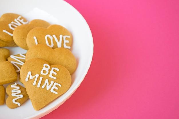 Platte mit köstlichen zuckerkeksen in herzform mit zuckerguss und worten der liebe und sei mein auf rosa hintergrund. frisch gebackene hausgemachte kekse, süßes geschenk für valentinstagfeier. speicherplatz kopieren.