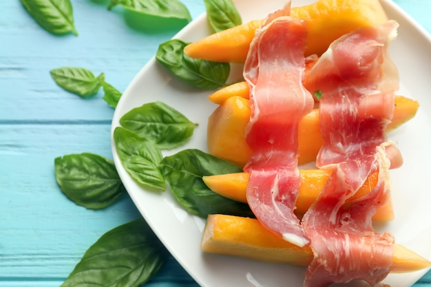 Platte mit köstlicher melone und schinken auf farbtisch