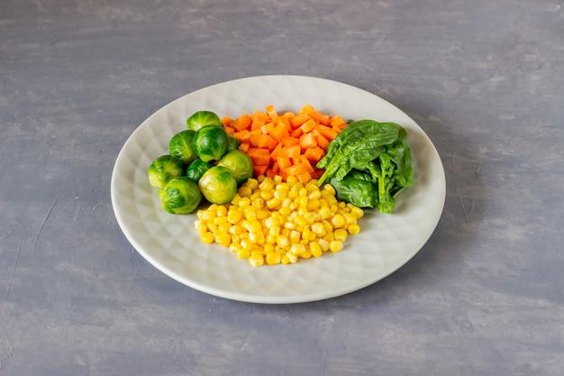 Platte mit kohl, karotten, mais und spinat