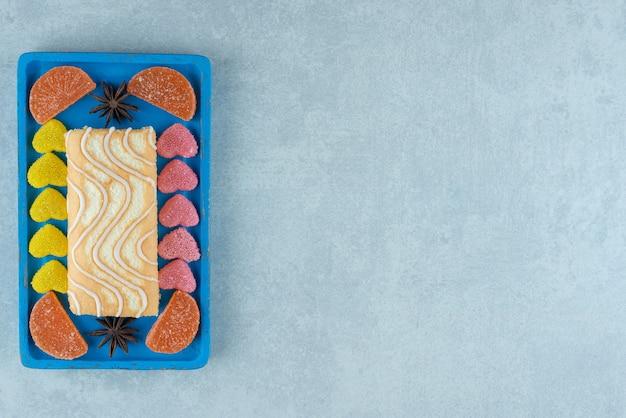 Platte mit kuchenrolle mit anis und marmeladenstücken auf marmor.
