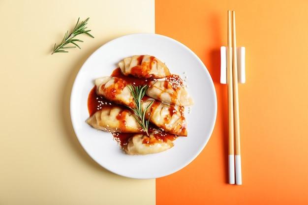 Platte mit leckerem japanischen gyoza und sauce auf farbe