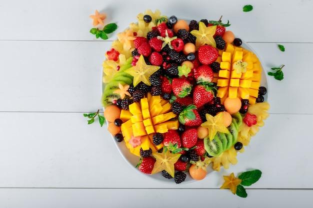 Platte mit mango, orangen, kiwi. erdbeeren, heidelbeeren.