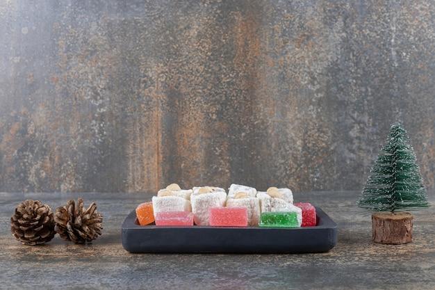 Platte mit marmeladen und türkischen köstlichkeiten neben einem tannenzapfen und einer baumfigur auf holzoberfläche