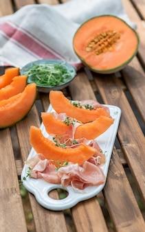 Platte mit melone und jamon, holztisch, snack