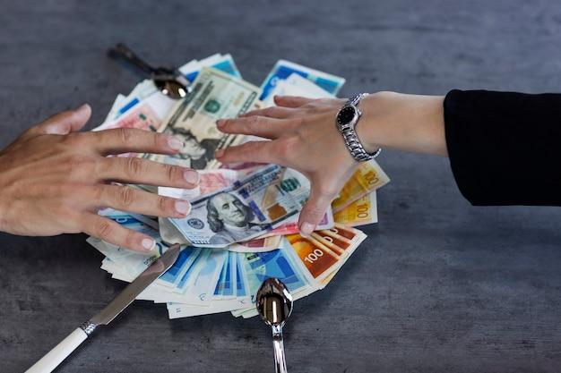 Platte mit neuen israelischen schekelscheinen. hand des mannes und bündel bargeld auf weißem teller auf dem tisch. konzept, das geldgier zeigt. geschäftsleute, die geld nis greifen. hände, die versuchen, geld zu ergattern