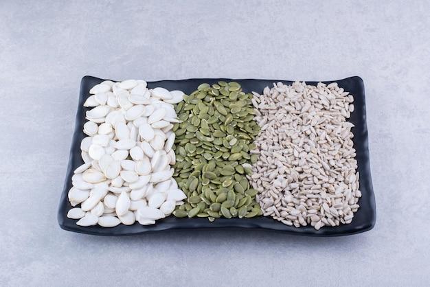 Platte mit pepitas, sonnenblumenkernen und weißen kürbiskernen auf marmoroberfläche