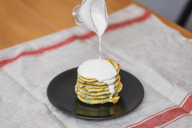 Platte mit pfannkuchenstapel und süßer sauce einschenken