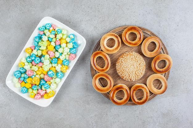 Platte mit popcornbonbons und einem einzelnen keks, umgeben von sushki auf einem holzbrett auf marmorhintergrund. hochwertiges foto