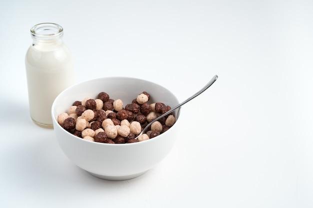 Platte mit runden weizen- und schokoladenflocken auf einer hellen oberfläche. seitenansicht mit platz zum kopieren. das konzept der richtigen ernährung.