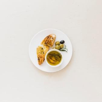 Platte mit scheibe brot öl und oliven