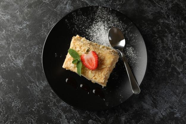 Platte mit stück napoleon-kuchen mit erdbeere auf schwarzer rauchiger oberfläche