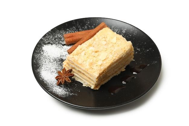 Platte mit stück napoleon-kuchen mit zimt auf weißer oberfläche isoliert