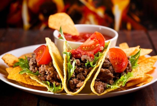 Platte mit taco, nachos-chips und tomatendip