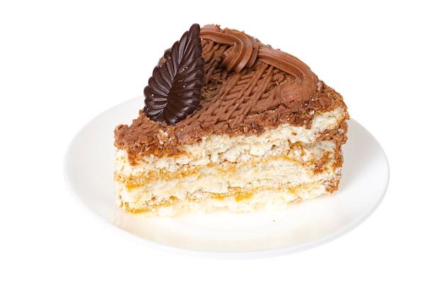 Platte mit teil des köstlichen hausgemachten kuchens verziert mit schokolade auf weißem hintergrund. studiofoto