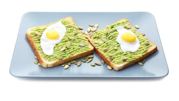 Platte mit toast, avocadopaste und spiegeleiern, isoliert auf weiß