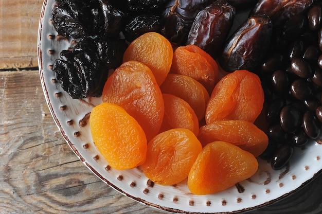 Platte mit trockenfrüchten auf einem hölzernen rustikalen