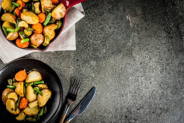 Platte und bratpfanne mit gebratenem saisonherbstgemüse (zucchini, kartoffeln, karotten, bohnen), auf schwarzer steintabelle