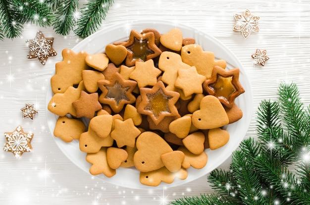 Platte voll des frisch gebackenen weihnachtslebkuchens bereit, mit zuckerglasur zu verzieren